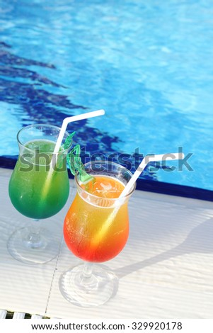 Glasses with colored cocktails are around the pool - stock photo