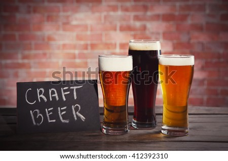 Glasses with different sorts of craft beer on brick wall background. Retro stylization - stock photo