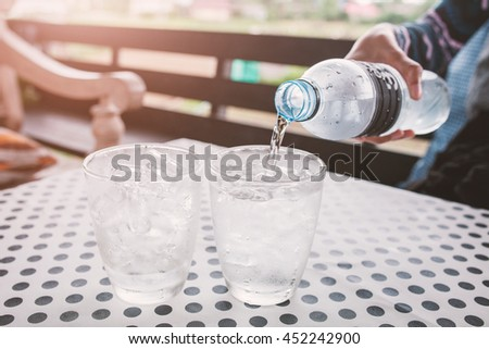 Glasses with ice cubes on black dot background table . - stock photo