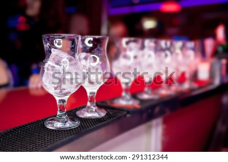 Glasses with ice on the bar counter at a nightclub - stock photo