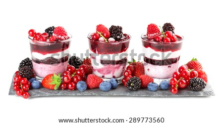 glasses with layered dessert and soft fruit on slate - stock photo