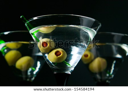 glasses with martini and green olives, focus on olives - stock photo