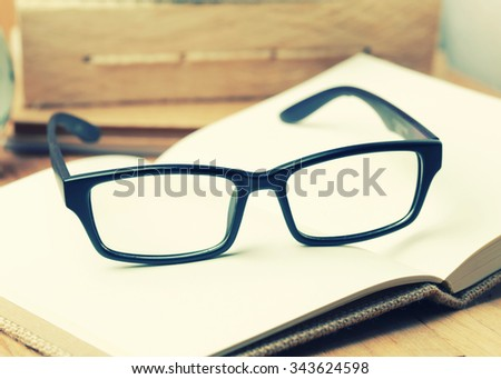 Glasses with note book on wood background.Vintage Style.