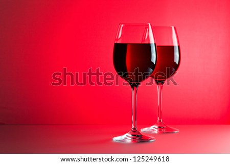glasses with red wine against of red background. - stock photo