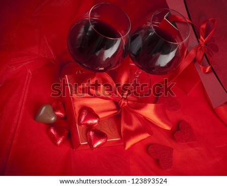 glasses with red wine on a red silk cover