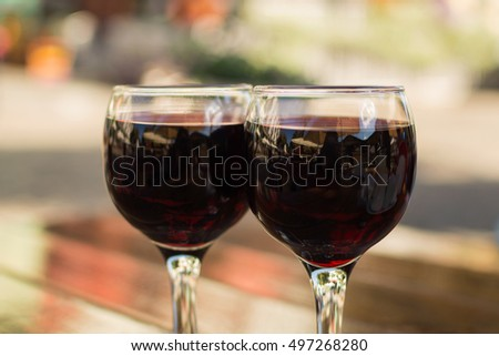 glasses with red wine on a table at an outdoor cafe with a blurred background