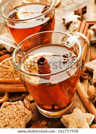Glasses with rooibos and hibiscus tea, spices and cookies. Shallow dof. - stock photo