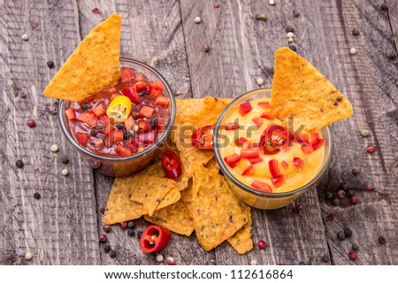 Glasses with Salsa- and Cheese Sauce on wooden background - stock photo