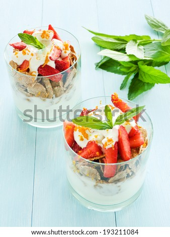 Glasses with strawberry parfait on the blue background. Shallow dof.  - stock photo