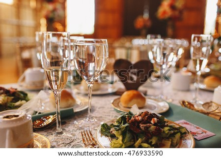 Glasses with water and champagne stand before a plate with salad