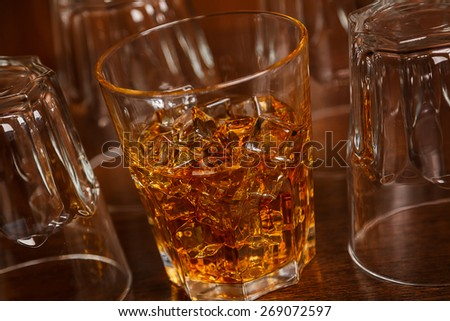 Glasses with whiskey on wooden bar counter