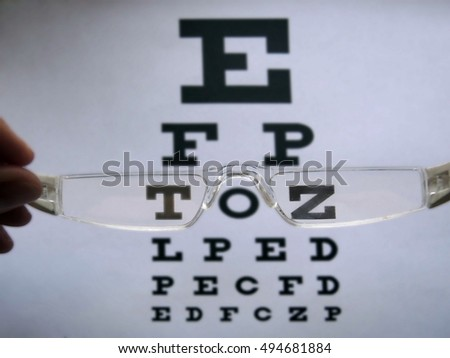 Glasses with white frame and eye test chart