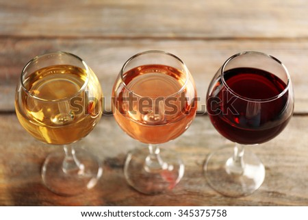 Glasses with white, rose and red wine on wooden background