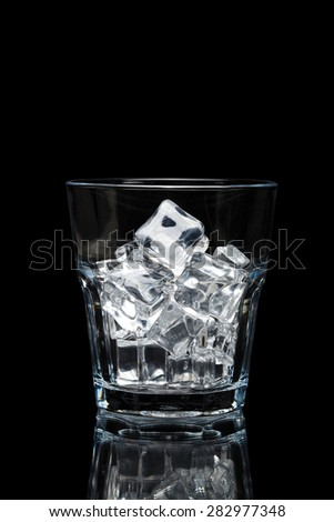 glassful for whiskey with ice cubes isolated on black background - stock photo