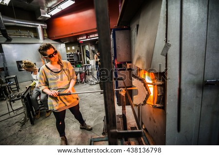 Glassmaker Flashing and Warming Piece of Glass in the Kiln with Blowing Pipe - stock photo