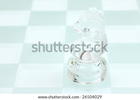 Glassy knight on the chess board - stock photo
