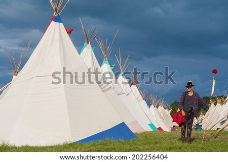 GLASTONBURY, UK - JUNE 28: A festival goers stands by a row of tipi tents at Glastonbury Festival on 28th June, 2014 at Pilton Farm, Somerset. - stock photo