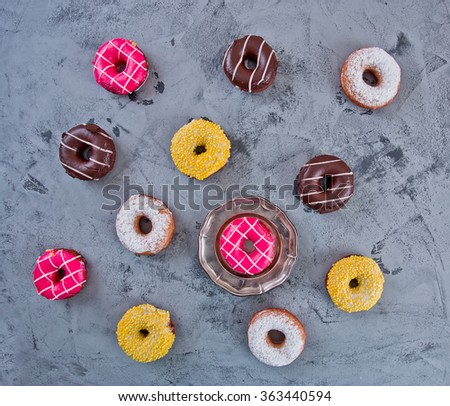 Glazed Doughnuts with colourful sprinkles and icing on dark background - stock photo