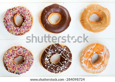 Glazed Doughnuts with colourful sprinkles, chocolate, icing on top of them. White background - stock photo