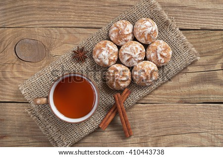 Glazed gingerbread with cup of hot tea on old wooden table, top view - stock photo