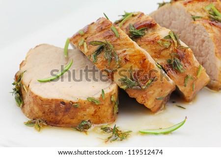 Glazed pork fillet on a white plate. Sliced pork tenderloin or sirloin in herbs and honey glaze - stock photo