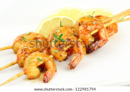 Glazed shrimp skewers with thyme on white plate - stock photo