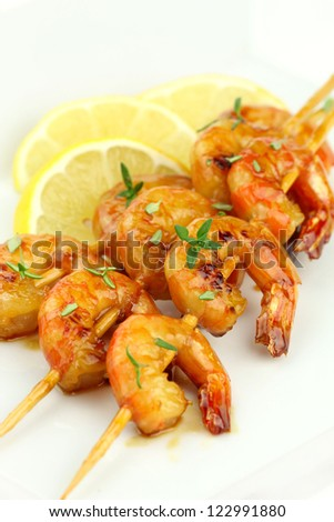 Glazed shrimp skewers with thyme on white plate