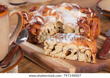 Glazed streusel coffee cake on a wooden cutting board