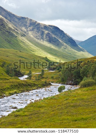 Glen Etive, a remote valley near Glencoe in the Scottish Highlands, where a ray of sunshine brightens the mountain slopes and the River Etive flows between banks lined with heather and bracken. - stock photo