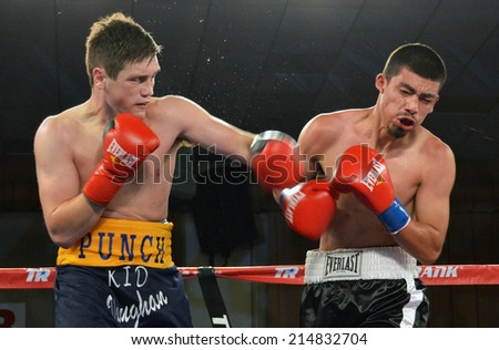 GLENDALE, CA - AUGUST 9, 2014: Boxer Liam Vaughn follows through on a punch which leaves his opponent Saul Benitez grimacing. The bout took place in Glendale, California on August 9, 2014. - stock photo