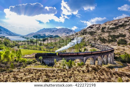 Glenfinnan Railway Viaduct in Scotland with the Jacobite steam train against sunset over lake - stock photo