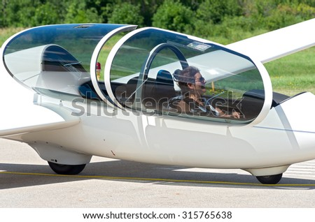 glider or sailplane passenger seated in cockpit waiting for takeoff from runway - stock photo