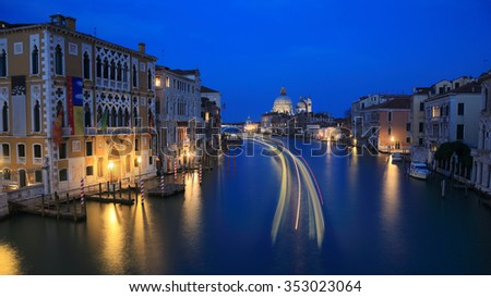 Gliding Into the Night of Beautiful Venezia ~ Evening view of Venice with light trails of ferry boats on Grand Canal and Basilica di Santa Maria della Salute in the distant background - stock photo