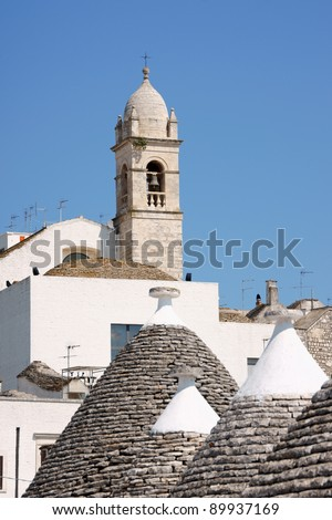 Glimpse of Alberobello, Apulia, Italy. A typical feature of Alberobello are the trulli houses made of white dry-stone with conical roofs made of lapidary stones. - stock photo