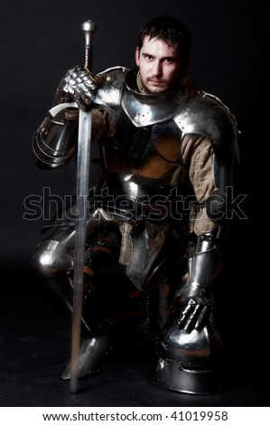 Glistening Knight with two-handed sword and helmet - stock photo