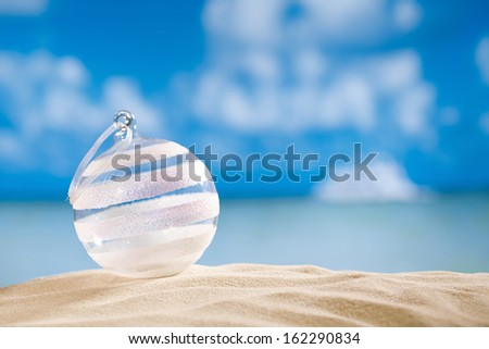 glitter christmas glass ball on  beach with seascape background - stock photo