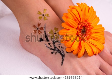 Glitter tattoo on a caucasian woman's leg. - stock photo