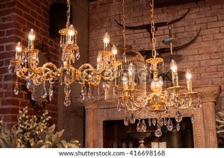 Glittering chrystal chandeliers hanging on the ceiling of an art and furniture shop.