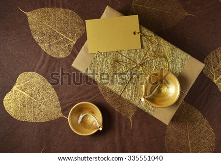 Glittering golden gift box with a blank tag and Indian traditional lamps. Diwali festive gift background. View from top. - stock photo
