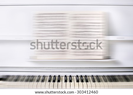 Glittering white beautiful piano in the front with notes on a stand  - stock photo