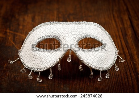 Glittering white carnival mask on wooden table - stock photo