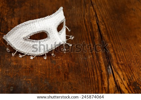 Glittering white mask on wooden table, rustic background - stock photo