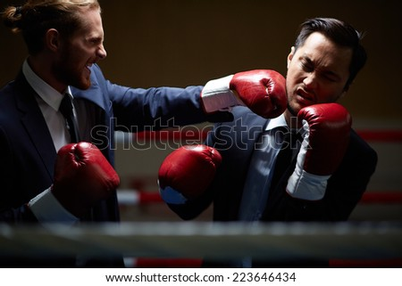 Gloating businessman fighting with rival - stock photo