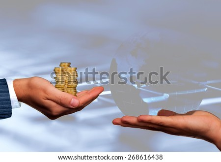 Global business concept. Hands with glass globe and coins over a computer keyboard. - stock photo