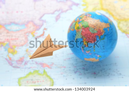 Global business image, paper airplane flying over world map - stock photo
