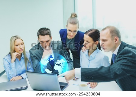 global business, technology and people concept - serious business team with laptop computers and virtual globe projection having discussion in office - stock photo