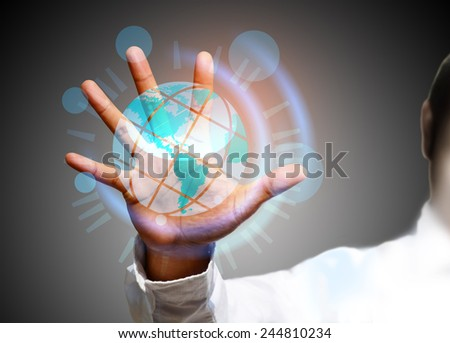 Global Communication - A businessman holding a glowing, connected, World. - stock photo