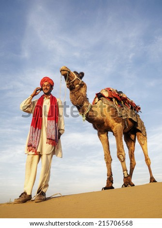 Global communications. Indian Guide and camel (Jonnie) in the desert. - stock photo