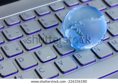 global computer business concept with small glass globe on gray laptop keyboard