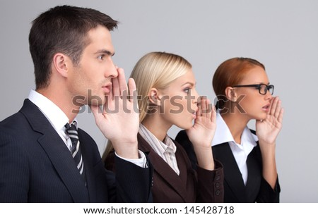 Global gossiping. Side view of three attractive young business people telling gossips standing with their hands covering mouth while isolated on gray - stock photo
